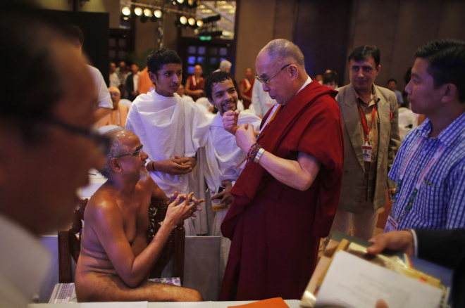 Tibetan spiritual leader the Dalai Lama, center, gestures as he speaks to Munishree Tarun Sagar, sitting, who represents the Digambar sect of Jainism, on the final day of an interfaith meeting in New Delhi, India, Sunday, Sept. 21, 2014. (AP Photo/Altaf Qadri)
